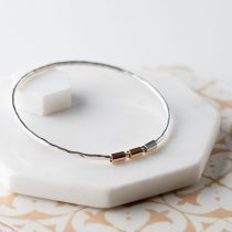 Sterling silver bangle, three tube beads. Silver, 9ct rose gold and 9ct yellow gold.