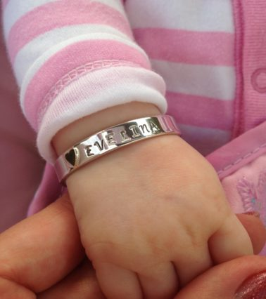 A silver baby cuff with a tiny gold heart and the stencilled word 'Evelina', shown on a baby wrist.